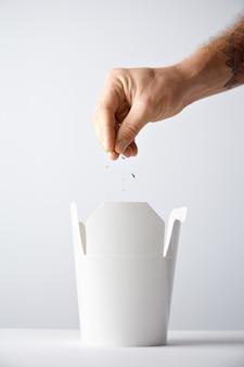 Proceso de cocción de fideos para llevar la mano vierte algunas especias dentro de la caja blanca en blanco con pasta wok