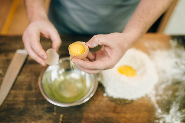Proceso de cocción de pasta, manos de chef masculino con huevo