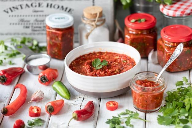 Proceso de cocción de salsa picante de pimientos rojos. ingredientes: pimienta, verduras, albahaca, pimentón sobre una mesa de madera. frascos de vidrio con salsa preparada.