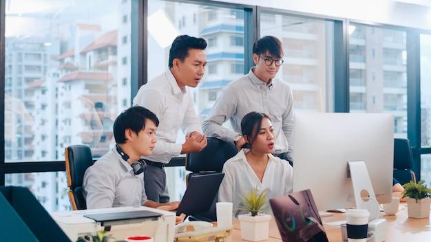 Proceso de colaboración de empresarios multiculturales que utilizan la presentación por computadora y la comunicación para encontrar ideas de lluvia de ideas sobre los colegas del proyecto y la estrategia de éxito del plan de trabajo en la oficina moderna.