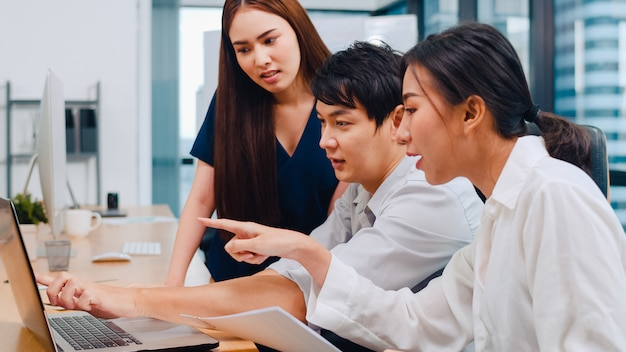 Proceso de colaboración de empresarios multiculturales que utilizan la presentación y la comunicación de una computadora portátil para reunir ideas de lluvia de ideas sobre los colegas del proyecto y la estrategia de éxito del plan de trabajo en la oficina moderna
