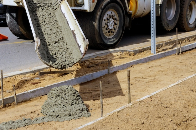 Proceso de construcción de acera de cemento recién vertido