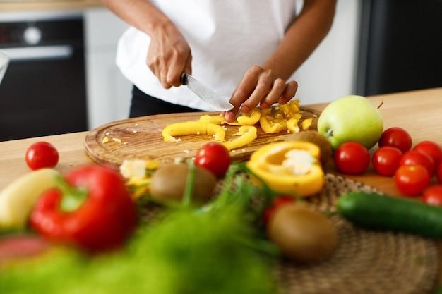 Proceso de cortar pimiento amarillo sobre la mesa, lleno de verduras y frutas.