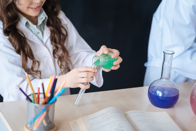Proceso de creación de algo único. adolescentes hábiles astutos diligentes de pie en el laboratorio y disfrutando del experimento de química mientras participan en el proyecto científico y exploran las bombillas
