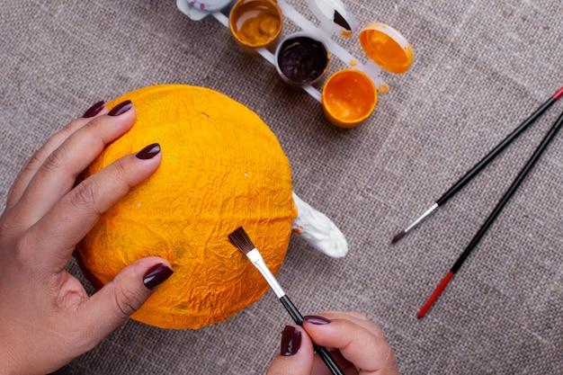 El proceso de creación de una calabaza de papel maché para decoración de halloween, dibujo de pintura, superficie de arpillera