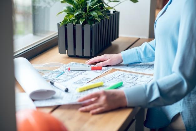 Proceso creativo. manos femeninas cerca de dibujos de esquemas y marcadores de colores en el alféizar de la ventana en el edificio a la luz del día, sin rostro