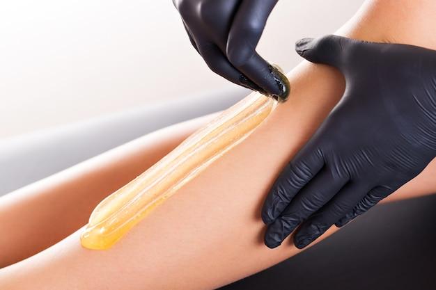 Proceso de depilación en la pierna femenina con depilación.