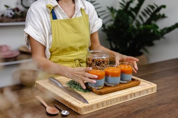 Proceso de elaboración del pudín de chía. capas de diferentes colores hechas de leche de almendras, semillas de chía, extracto de súper alimento de espirulina azul y mermelada de papaya y mango.