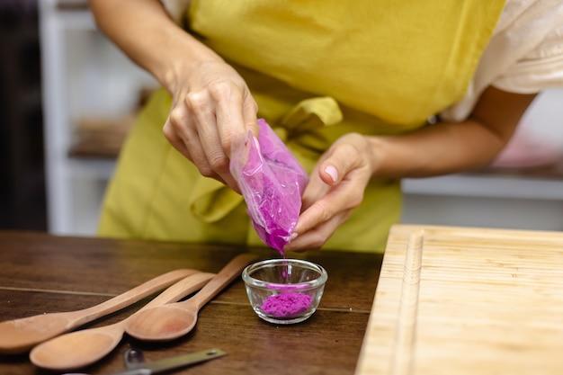 Proceso de elaboración de pudín de chía desayuno saludable. mujer mezcla semillas de chía, leche de almendras y extracto de fruta de dragón de color natural en licuadora.