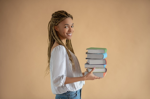 Proceso de estudio. feliz joven mujer afroamericana llevando pila de libros delante de ella