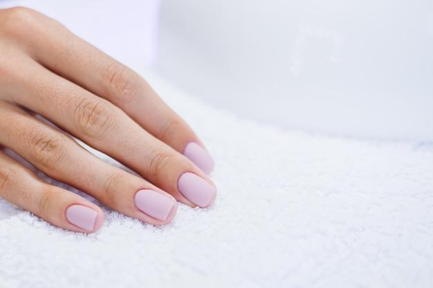 Proceso de fabricación de tratamiento de uñas de manos femeninas hermosas taladro de lima de uñas profesional en acción concepto de cuidado de la belleza y las manos