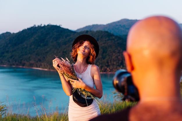 Proceso de grabación de video hombre tomar un video en cámara profesional de blogger joven y elegante en vacaciones vista tropical