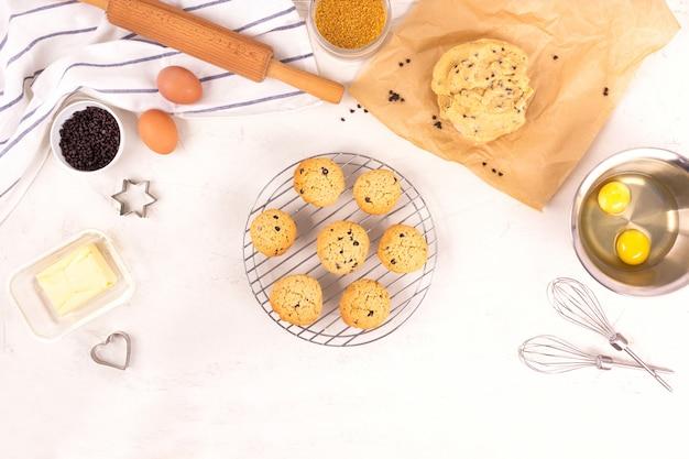 El proceso de hacer galletas, paso a paso. equipos e ingredientes culinarios. huevos, harina, azúcar, chocolate, mantequilla, utensilios para hornear. lay flat.