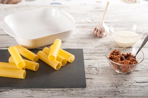 El proceso de hacer pasta. pasta de canelones cruda en un primer plano de la mesa de luz y espacio de la copia.