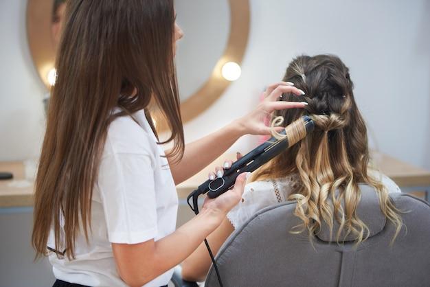 Proceso de hacer peinado de moda en salón de belleza.