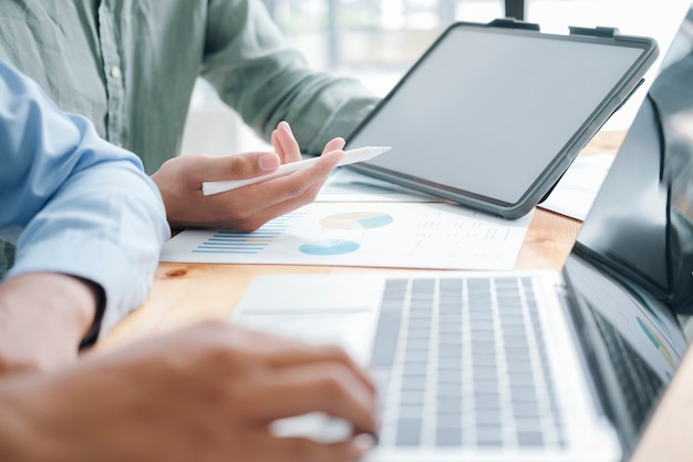 Proceso de lluvia de ideas y discusión. foto de un equipo de jóvenes empresarios trabajando con un nuevo proyecto de inicio. hombre que sostiene la tableta de pantalla en blanco.