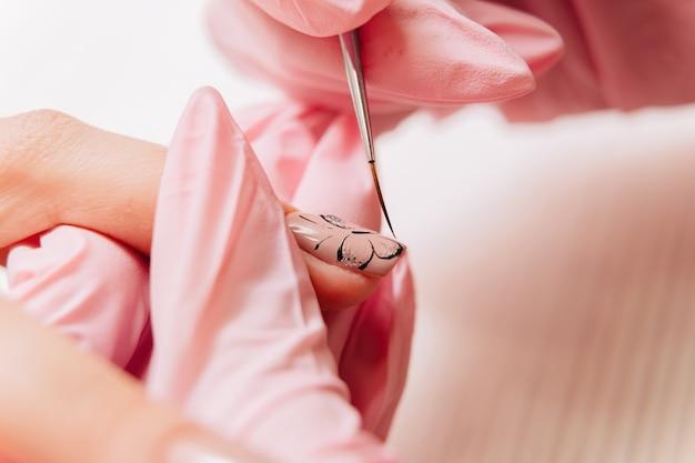 Proceso de manicura. el maestro dibuja un dibujo de mariposa en la uña con un pincel fino.