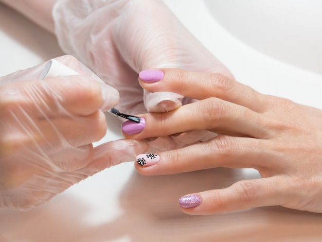 Proceso de manicura. manicura creativa con coronavirus pintado en las uñas.