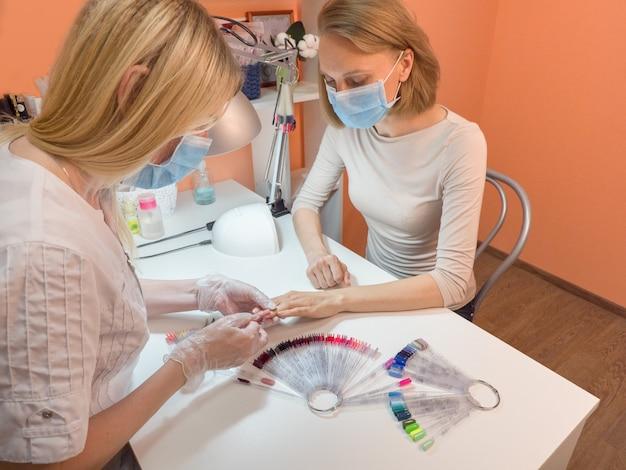 El proceso de manicura. trabajo en una máscara médica, protección contra la pandemia.