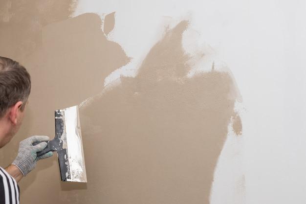 Proceso de masilla de muro de hormigón con una espátula de metal