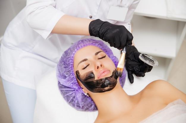 Proceso de pelado con láser de carbón en salón de belleza los pulsos láser limpian la piel de la cara. tratamiento de cosmetología de hardware. rejuvenecimiento de piel. mujer joven con nanogel de carbono en la cara