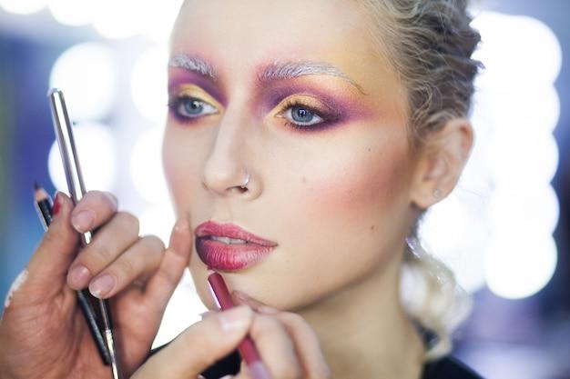 Proceso de primer plano creativo retrato de moda y belleza. maquillaje creativo de una mujer joven y bella. maquilladora