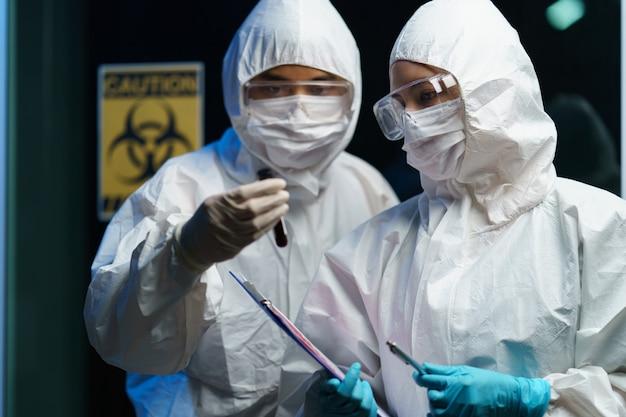 Proceso de prueba de coronavirus: científico de la pareja con una máscara médica con gafas de seguridad en traje de materiales peligrosos, sosteniendo un tubo de muestras de análisis de sangre en el informe con información sobre el análisis de sangre.