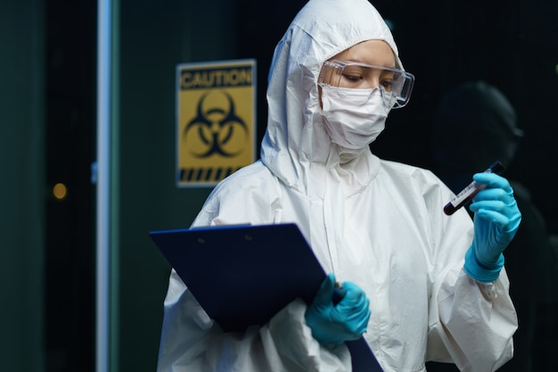 Proceso de prueba de coronavirus: mujer científica que usa una máscara médica con gafas de seguridad en traje de materiales peligrosos, con un tubo de muestras de análisis de sangre en el informe con información sobre el análisis de sangre.