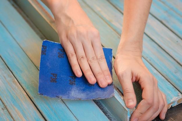 Proceso de pulido a mano de superficie de tablero de madera con papel de lija. Foto Premium