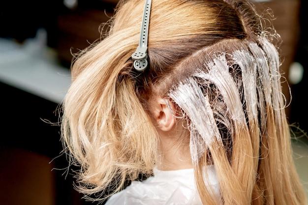 Proceso de teñir el cabello de la mujer.