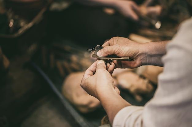 Proceso de trabajo artesanal de artista sénior detalle muy fino acabado pulido producto hecho a mano a mano.