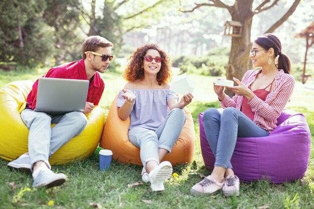 Proceso de trabajo. compañeros ambiciosos alegres sentados al aire libre y trabajando en el proyecto