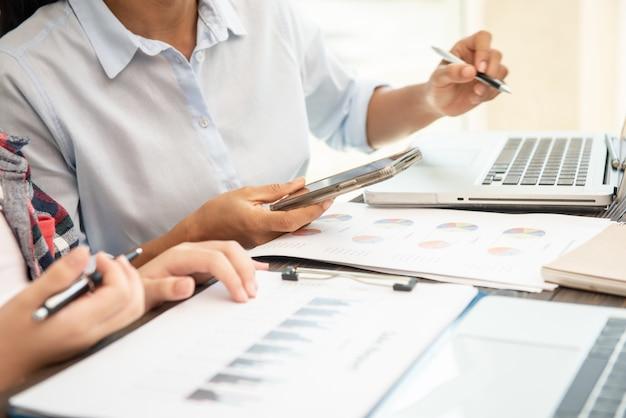Proceso de trabajo en equipo. empresarios discutiendo los cuadros y gráficos que muestran los resultados de su cooperación exitosa