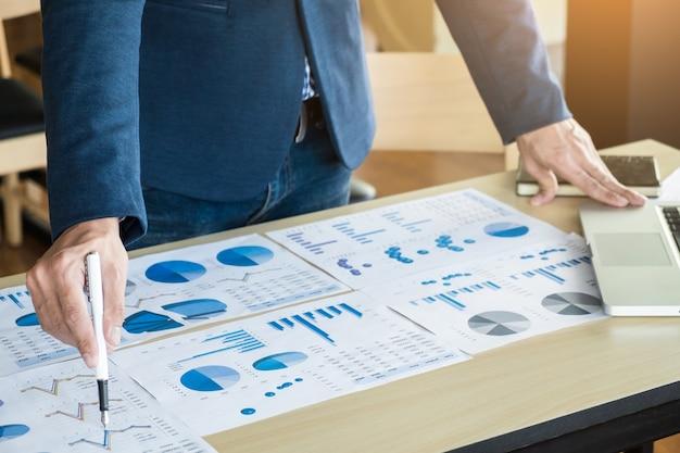 Proceso de trabajo en equipo. joven equipo de gerentes de negocios trabajando con el nuevo proyecto de inicio. labtop en la tabla de madera, tecleando el teclado, mensaje texting, analiza planes del gráfico.