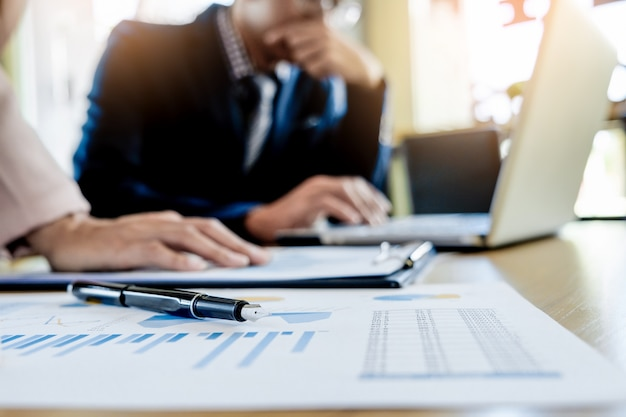 Proceso de trabajo en equipo. joven equipo de gerentes de negocios trabajando con el nuevo proyecto de inicio. ordenador portátil en la tabla de madera, tecleando el teclado, mensaje texting, analiza planes del gráfico.