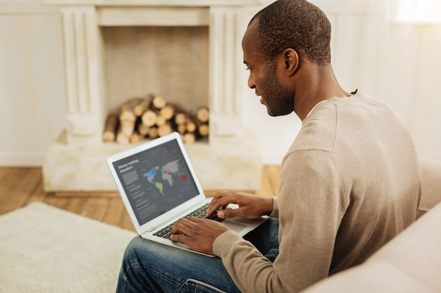 Proceso de trabajo. feliz hombre afroamericano de ojos oscuros sonriendo y trabajando en la computadora portátil mientras está sentado en el sofá y una chimenea en el fondo