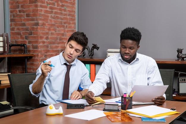 Proceso de trabajo de vista frontal dos hombres de negocios que trabajan en la oficina moderna