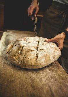 Producción de pan horneado con horno de leña en una panadería.