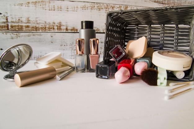 Producto de belleza cosmética derramado de cesta de mimbre sobre mesa