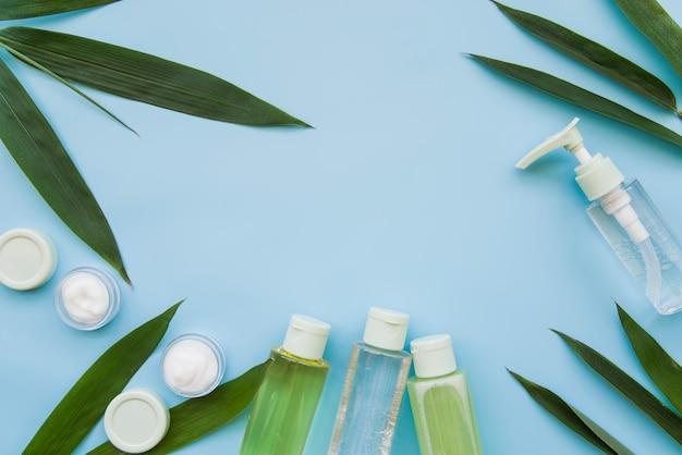 Producto de belleza natural decorado con hojas sobre fondo azul.