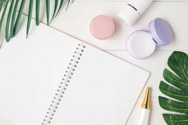 Producto cosmético y cuidado de la piel y cuaderno y hojas sobre mesa.