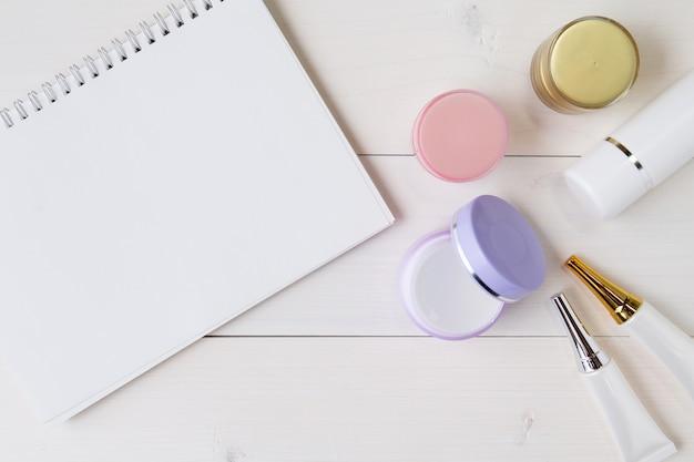 Producto cosmético y cuidado de la piel y cuaderno sobre mesa de madera blanca