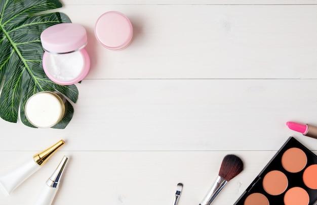 Producto cosmético y cuidado de la piel y hojas verdes en mesa de madera blanca.