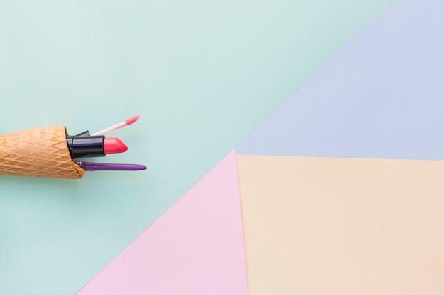 Producto cosmético del maquillaje en cono de helado en diverso fondo coloreado