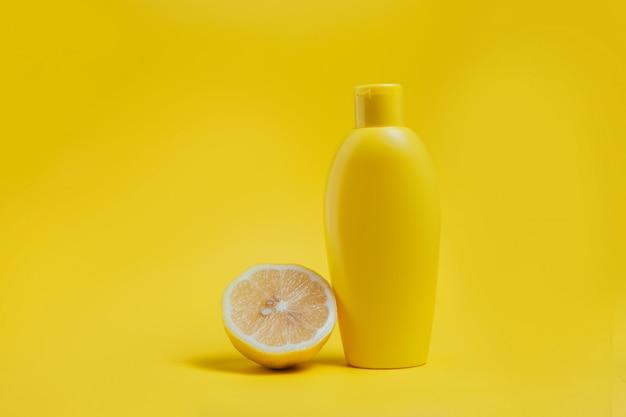 Producto para el cuidado del cuerpo y limón sobre amarillo