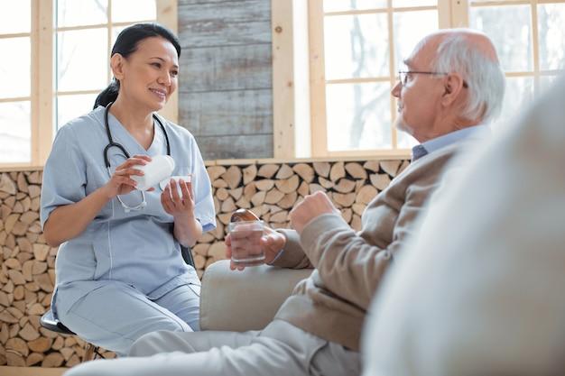 Producto medicinal. doctor alegre alegre sentado en una silla y riendo mientras mira al hombre mayor