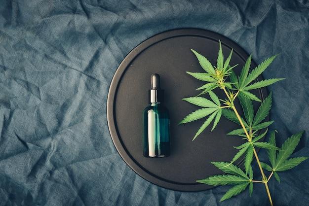 Producto médico cannabs, aceite de cbd, con hojas de cáñamo en un plato negro