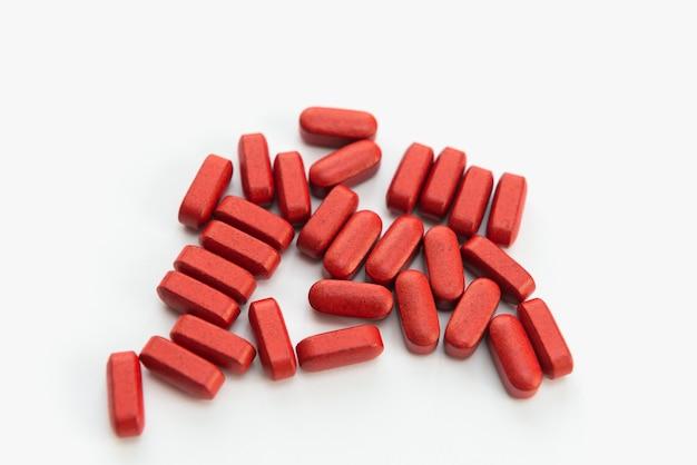 Producto médico en pastillas rojas sobre un fondo blanco.