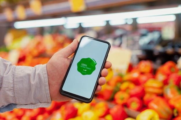 Producto natural. un hombre sostiene un teléfono inteligente en sus manos con una etiqueta en la pantalla sobre el fondo de verduras frescas en una vitrina en un supermercado. comida sana y respetuosa con el medio ambiente.
