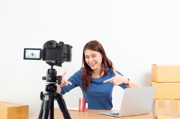 Producto de revisión de mujer asiática en vivo con cámara digital en línea